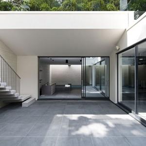 """Alternatywą dla tradycyjnych drzwi stały się duże, szklane panele przesuwane, przez które przenika naturalne światło. """"Wpada"""" do szarego wnętrze, dzięki czemu jest ona jaśniejsze. Projekt: Rupert Martineau, SHH Architects. Fot. Alastair Lever, Gareth Gardner."""