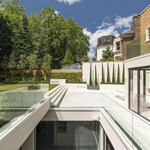 Nowoczesnym dodatkiem do tradycyjnej bryły budynku było zamontowanie szklanych balustrad oddzielających parter od okolicy przydomowej i ogrodu. Projekt: Rupert Martineau, SHH Architects. Fot. Alastair Lever, Gareth Gardner.