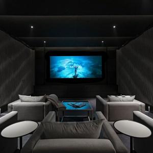 Na życzenie właścicieli w domu powstałą też sala kinowa z prawdziwego zdarzenia. Ciemne, wytłumione akustycznie wnętrze oświetlone zostało lekkimi światłami. Projekt: Rupert Martineau, SHH Architects. Fot. Alastair Lever, Gareth Gardner.