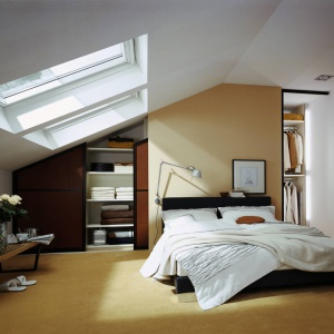 Sypialnia ze skosami nie musi być trudna w aranżacji. Ściany w miejscu gdzie sufit się obniża, warto zagospodarować pakowną szafą. Fot. Raumplus.