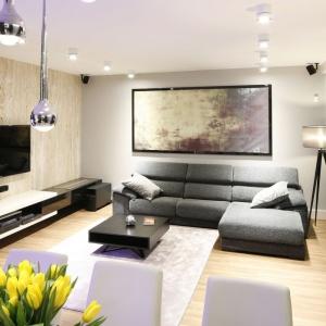 W salonie dominują stonowane barwy ziemi. W tę kolorystykę doskonale wpisuje się jasny trawertyn na ścianie z telewizorem. Projekt: Monika i Adam Bronikowscy. Fot. Bartosz Jarosz.