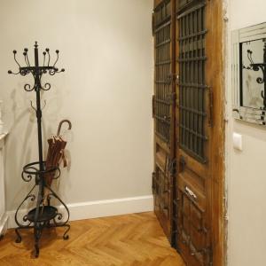 W starej kamienicy bardzo wąski korytarz urządzono w bieli i szarościach. Zachowane oryginalne drzwi wejściowe wraz ze stylowym wieszakiem budują niepowtarzalny klimat strefy wejścia. Projekt: Iwona Kurkowska. Fot. Bartosz Jarosz.