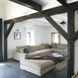 Jasne obicie kanapy w połączeniu z belkami i kolorem poduch na kanapie to wyeksponowanie naturalnych materiałów, na których zależało właścicielom.