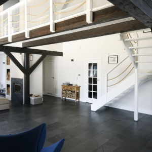 """Ciemna podłoga z łupka w połączenie z belkami """"podtrzymującymi"""" sufit tworzy ciekawe połączenie z marynistyczną bielą ścian i schodów prowadzących na piętro domu."""