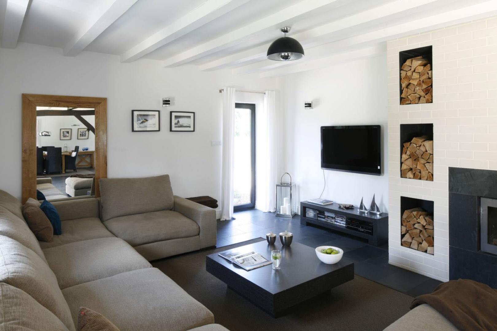 Duża kanapa to dobre rozwiązanie by móc wygodnie odpoczywać przy cieple kominka. Nadaje wnętrzu naturalnego charakteru oraz wyraźnego kontrastu wobec klasycznej bieli i czerni.