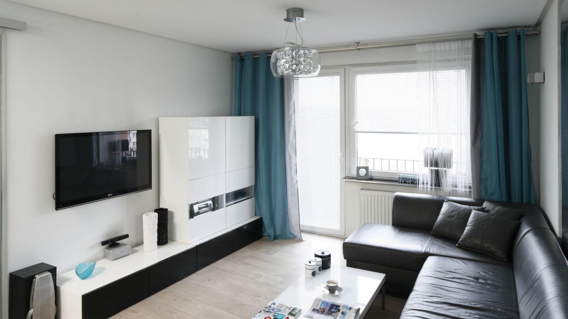 Meble umieszczone w salonie są wyrazem nowoczesności poprzez charakterystycznie zarysowane kształty i fronty na wysoki połysk. Eleganckim akcentem jest tutaj czarny kolor frontu na szafce RTV.