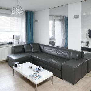 Skórzana, ciemna sofa nadaje wnętrzu elegancji i wyrafinowania. Stolik kawowy, który swoją formą nawiązuje do nowoczesności i minimalizmu, jest - dla kontrastu, biały.