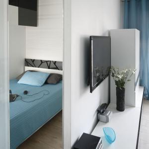 Pomysłowe rozwiązanie do małego wnętrza to umieszczenie pokoju sypialnianego za ścianą salonu, ukrytego za przesuwanymi drzwiami z mlecznego szkła.