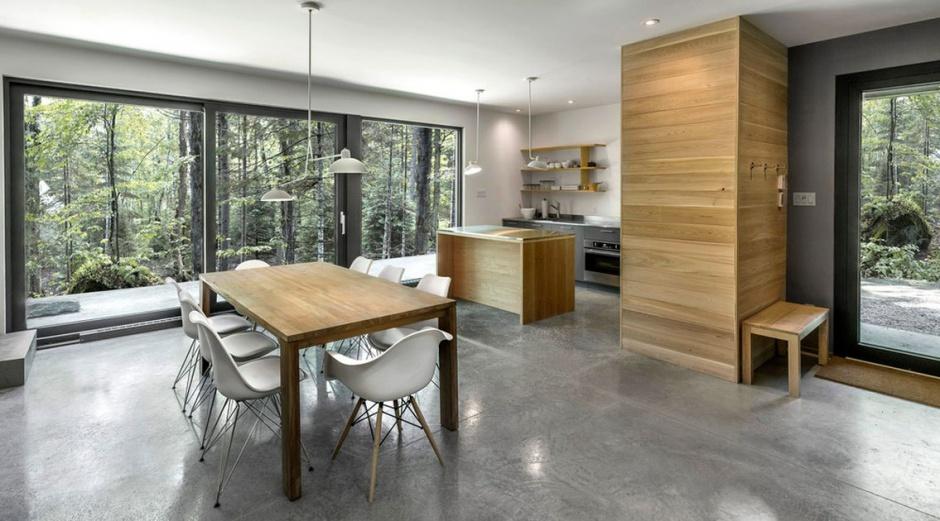 Kuchnia otwiera się na jadalnię, z którą spaja ją wizualnie betonowa podłoga. Projekt: Projekt: YH2. Fot. Julien Perron-Gagné.