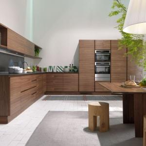Zabudowa kuchenna została wykonana z prawdziwego litego drewna w głębokim ciemnym wybarwieniu. Nadaje przestrzeni elegancki, przytulny charakter, harmonizując z drewnianym stołem i stołkami/pieńkami. Fot. La Cucina.