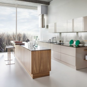 Model kuchni Z2 to połączenie frontów polakierowanych na wysoki połysk w jasnym kolorze kawy z mlekiem z frontami wykończonymi naturalnym fornirem drewna orzechowego. Fot. Zajc Kuchnie.