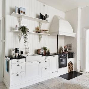 Kuchnię urządzono w stylu skandynawskim, z elementami typowymi dla wnętrz w stylu angielskim. Angielski charakter buduje bateria, zlewozmywak i zdobny okap. Fot. Stadshem.se/Jonas Berg.