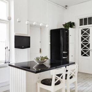 W centrum kuchni stanęła praktyczna wyspa. Biały korpus mebla wieńczy elegancki, czarny blat, idealnie harmonizującymi z ciemnymi obiciami wysokich stołków. W kącie pomieszczenia - modna, wolno stojąca lodówka w stylu retro. Fot. Stadshem.se/Jonas Berg.