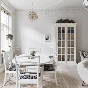 Salon połączono z jadalnią, usytuowaną w bliskim sąsiedztwie dwóch dużych okien. Białemu stołowi towarzyszą białe krzesła z ciemnymi, tekstylnymi obiciami. Fot. Stadshem.se/Jonas Berg.