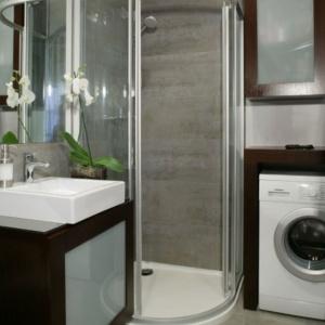Narożna kabina zapewnia oszczędność miejsca: w łazience zmieściła się również pralka. Projekt: Karolina Pawłowicz. Fot. Monika Filipiuk-Obałek.