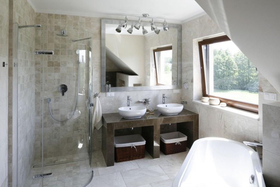 Salon kąpielowy w beżach wyposażono w narożną kabinę prysznicową, która jest niemal niewidoczna na tle ściany. Projekt:  Beata Ignasiak. Fot. Bartosz Jarosz.