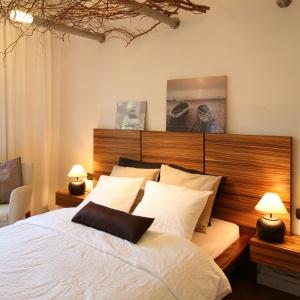 Drewno to doskonały materiał do dekoracji sypialni. Dodaje wnętrzom ciepła i przytulności. Sprawdzi się również jako dekoracyjny zagłówek. Projekt: Urszula i Jakub Górscy. Fot. Bartosz Jarosz.