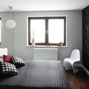 Lustro na ścianie sprawi, że wnętrze będzie wyglądało na znacznie większe. Dodatkowo również je rozjaśni. To dobre rozwiązanie do sypialni, w której ściany są wykończone ciemnym kolorem. Projekt: Agnieszka Burzykowska-Walkosz. Fot. Bartosz Jarosz.