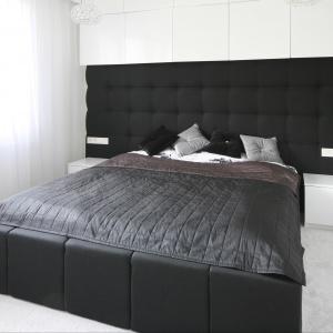 Sypialnia urządzona w czerni i bieli. Piękny dekoracyjny zagłówek rozciągnięty na całą szerokość ściany to ciekawy element wnętrza. Projekt: Dominik Respondek. Fot. Bartosz Jarosz.