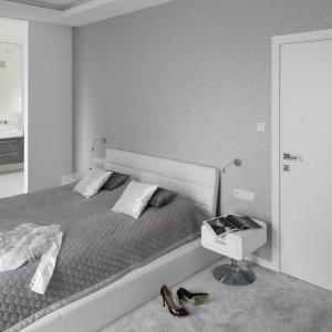 Jasna sypialnia połączona z łazienką. Wnętrze zainspirowane jest stylistyką nowoczesną. Proste w formie meble, a także stolik nocny na metalowej nodze świetnie uzupełnia aranżację. Projekt: Katarzyna Mikulska-Sękalska. Fot. Bartosz Jarosz.