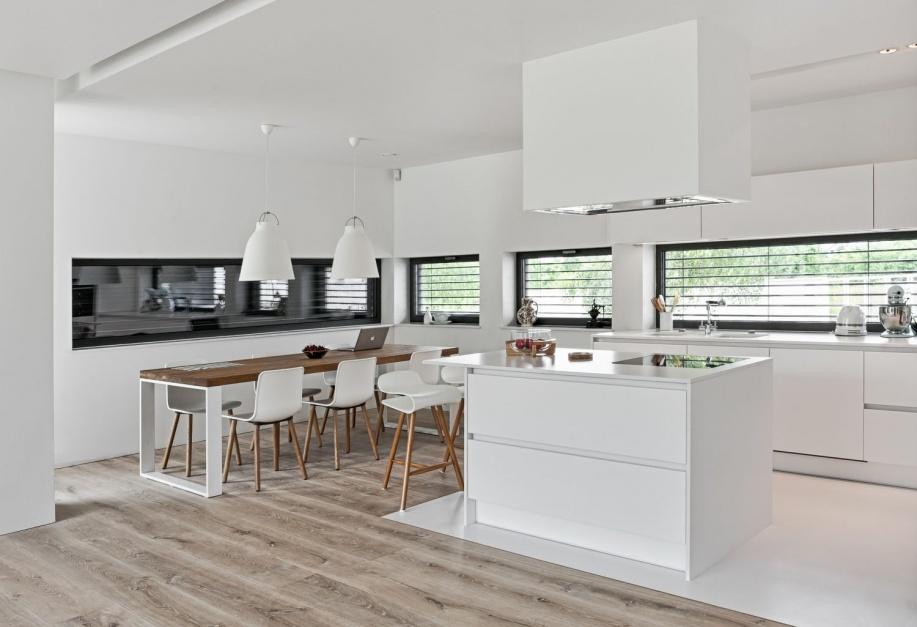 Biała kuchnia otwarta na jadalnię ma w centrum dużą wyspę, ustawioną prostopadle do stołu jadalnianego. Przy dużym meblu, na którym urządzono powierzchnię gotowania ustawiono hokery i urządzono bar. Fot. Atlas Kuchnie.