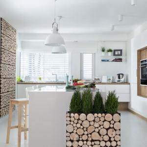 W tej przestronnej kuchni bar, urządzony na wyspie kuchennej, stanowi centrum całego pomieszczenia. Ponieważ wnętrze urządzone jest w bieli, ocieplonej motywami drewna, hokery mają formę stołków z surowego drewna. Fot. Max Kuchnie, Pracownia Mebli Vigo.