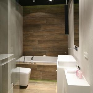 Biel, jasna szarość i płytki jak drewno – łazienka sprawia wrażenie przestronnej. Ciemny sufit obniża optycznie wysokie pomieszczenie. Projekt: Dominik Respondek. Fot. Bartosz Jarosz.