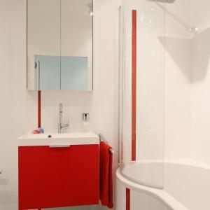 Biel optycznie powiększa mała łazienkę. Wanna z parawanem umożliwia kąpiel pod prysznicem. Projekt: Iza Szewc. Fot. Bartosz Jarosz.