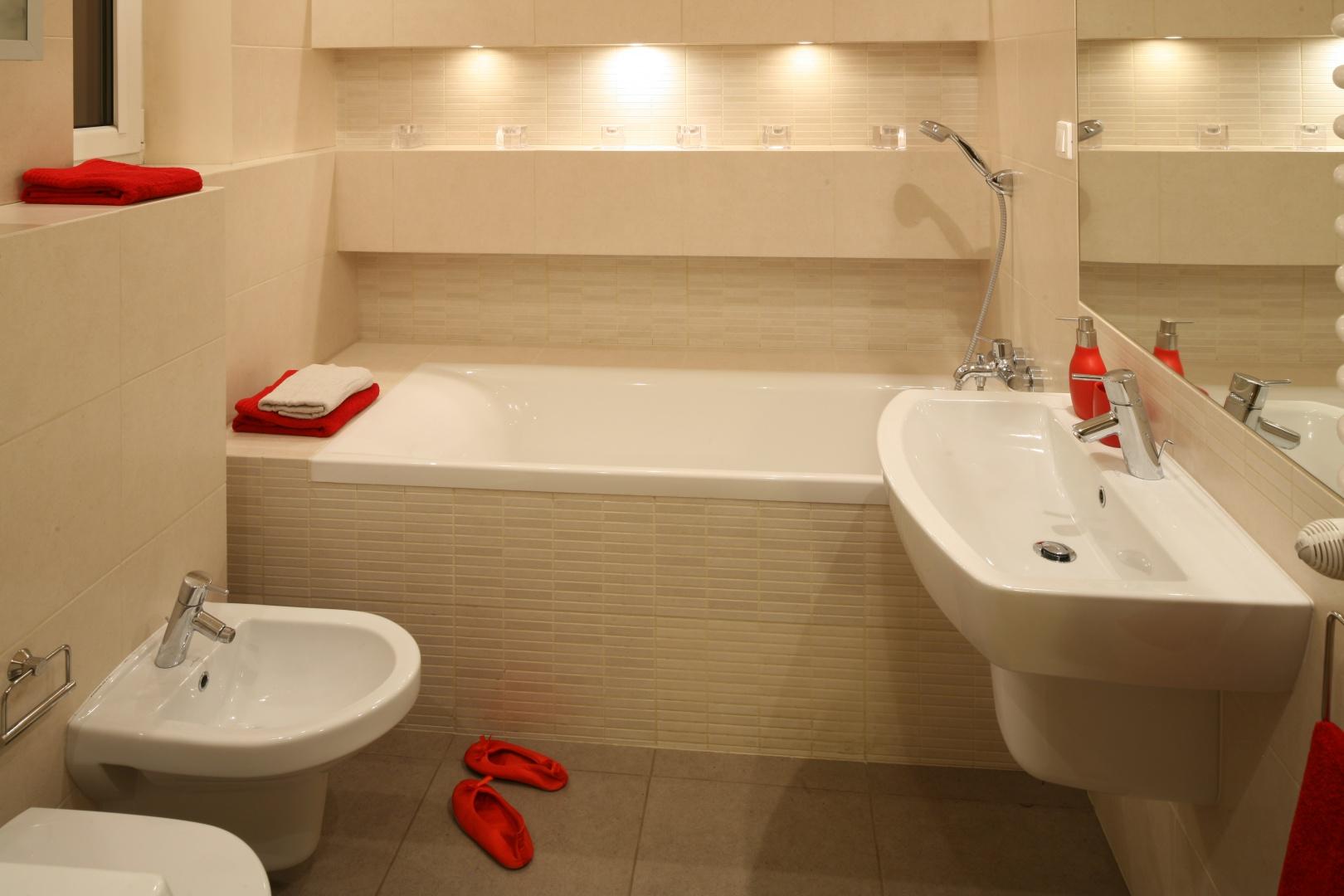 Powierzchnia 5,5 metrów kwadratowych. Rodzinna łazienka z dużą wanną, pralką i szafkami ukrytymi przy drzwiach. Projekt: właściciele. Fot. Bartosz Jarosz.