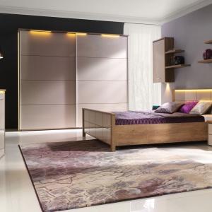 Sypialnia Wien to ciepłe, jasne drewno połączone z bielą na wysoki połysk. Charakteru kolekcji dodaje subtelne oświetlenie wbudowane w bryły. Fot. Stolwit.