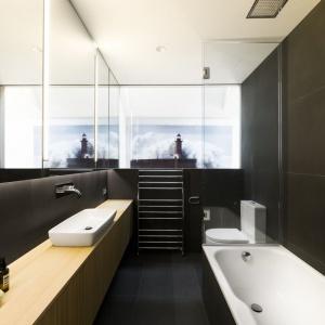 Choć niemal całe wnętrze skąpano w słońcu i jasnych barwach, w łazience króluje czerń, ocieplona - jak cały dom - drewnianymi elementami. Projekt: Mitsuori Architects. Fot. Michael Kai Photography.