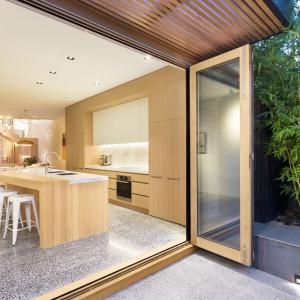 Kuchnia otwiera się na taras, a jednolita posadzka na zewnątrz i wewnątrz domu integruje wizualnie otoczenie budynku z jego wnętrzem. Projekt: Mitsuori Architects. Fot. Michael Kai Photography.
