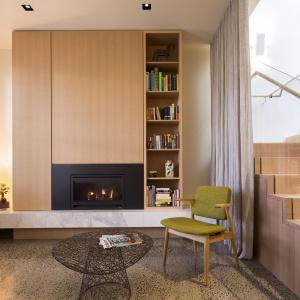 W przestrzeni obok schodów urządzono niewielki kącik, w którym można wypocząć i zrelaksować się przy kominku. Projekt: Mitsuori Architects. Fot. Michael Kai Photography.