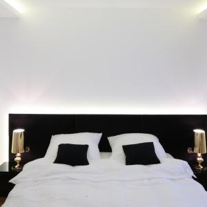 Białą, minimalistyczną sypialnię warto podkreślić przykuwającym wzrok detalem. Oświetlenie umieszczone za wezgłowiem łóżka nada wnętrzu charakteru, ale też będzie wspaniałym dodatkowym źródłem światła. Projekt: Agnieszka Hajdas-Obajtek. Fot. Bartosz Jarosz.
