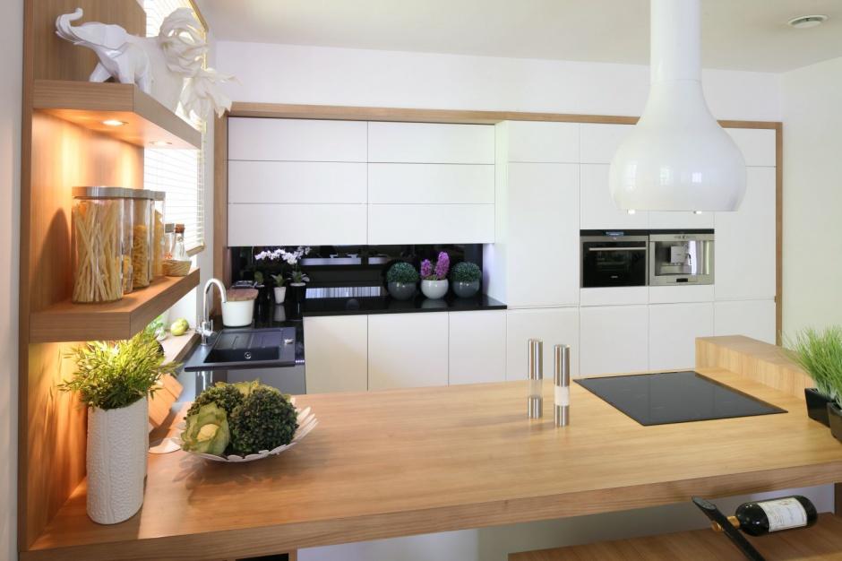 Nowoczesna kuchnia z zabudową utrzymaną w prostym stylu i białym kolorze. Całość ocieplono blatem, pozornie wyglądającym na drewniany, ale wykonanym z granitu. Projekt: Małgorzata Błaszczak. Fot. Bartosz Jarosz.