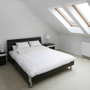 Nowoczesna sypialnia na poddaszu. Łóżko ustawiono tuż przy oknie, dzięki czemu miejsce relaksu za dnia jest dobrze doświetlone, a w nocy możemy podziwiać rozgwieżdżone niebo. Projekt: Magdalena Biały. Fot. Bartosz Jarosz.