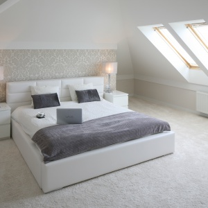 Sypialnię na poddaszu warto urządzić w bieli. Będzie wówczas bardzo jasnym, słonecznym pomieszczeniem, a do tego optycznie będzie wyglądać na znacznie większą. Projekt: Karolina i Artur Urban. Fot. Bartosz Jarosz.