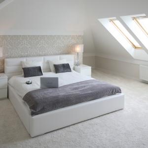 Sypialnia pod skosem to doskonały azyl dla męża i żony. Łóżko ustawione w centralnym punkcie wnętrza jest pięknie wyeksponowane. Projekt: Karolina i Artur Urban. Fot. Bartosz Jarosz.