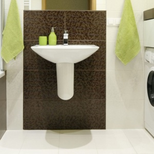 Wąska łazienka w bloku ma praktyczny parawan nawannowy oraz schowek na pralkę. Projekt: Marta Kilan. Fot. Bartosz Jarosz.