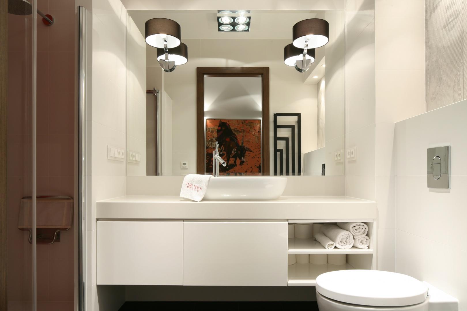 Mimo, że łazienka jest wąska, przestrzeni dodają jej jasna kolorystyka oraz spora tafla lustra w strefie umywalki. Projekt: Małgorzata Galewska. Fot. Bartosz Jarosz.