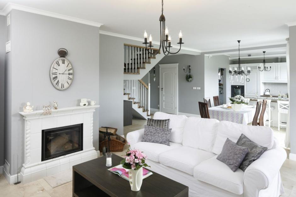 Szary kolor ma swój odpowiednik również w poduchach umieszczonych na kanapie, natomiast biel kanapy idealnie łączy się z białym kolorem kominka.