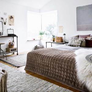 Miękka narzuta z wypukłym motywem, puszyste dodatki oraz duża ilość poduszek sprawią, że sypialnia nabierze wyjątkowo przytulnego klimatu. Fot. Broste Copenhagen.