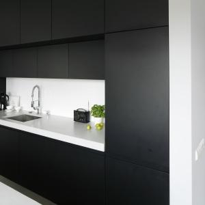 Czarne, matowe fronty kuchennej zabudowy wieńczy zimny, betonowy blat, który nadaje kuchni minimalistyczny charakter.