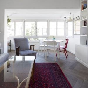 Podłogę w salonie i jadalni wykończono klasycznym, drewnianym parkietem, który pięknie ociepla dominującą we wnętrzach biel. Projekt: Studio Raanan Stern. Fot. Gidon Levin.