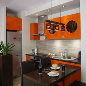 Oryginalny sposób na górną zabudowę kuchenną. Pomarańczowe fronty w wysokim połysku dodatkowo urozmaicają przeszklenia o okrągłym kształcie. Jest pomysłowo i odważnie. Projekt: Jolanta Kwilman. Fot. Bartosz Jarosz.