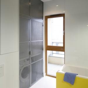 W łazience w stylu loft drzwi wysokiej zabudowy są wykonane z metalowej siatki. Wewnątrz jest domowa pralnia. Projekt: Monika i Adam Bronikowscy. Fot. Bartosz Jarosz.