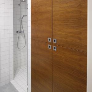 Szafa łazienkowa w małej łazience z prysznicem – w środku  są schowane kosmetyki i środki czystości. Projekt: Marta Kruk. Fot. Bartosz Jarosz.