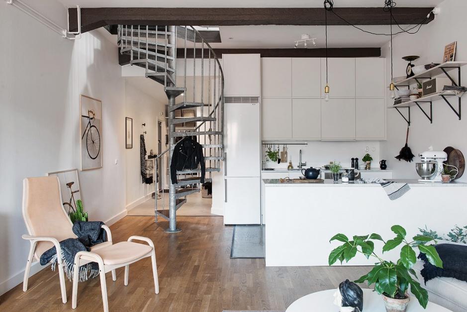 Wystrój wnętrza bazuje na stylistyce skandynawskiej z mocnymi akcentami w stylu loft. Odsłonięte belki stropowe, edisonowskie żarówki i metalowe schody, znajdujące się w centrum pierwszej kondygnacji budują w mieszkaniu industrialny klimat. Fot. Alvhem Makleri/Frederick J. Karlsson.