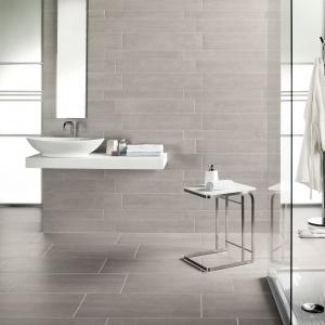 Aranżację cechuje oszczędny minimalizm. Na tle szarych płytek w różnych formatach świetnie prezentują się modne elementy wyposażenia łazienki. Na zdjęciu: płytki ZerMatt marki NovaBell. Fot. NovaBell.