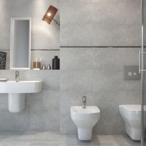 Klasyczna ceramika sanitarna została wyeksponowana na tle płytek przypominających beton. Wnętrze ocieplają starannie dobrane, minimalistyczne dodatki. Na zdjęciu: seria Bino firmy Cersanit. Fot. Cersanit.